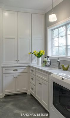 White and gray laundry room features white cabinets paired with gray and white marble countertops and backsplash.