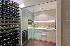 Wine cellar and a small kitchen connected visually using sliding glass doors - Decoist