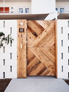 The way the offset concrete blocks create little window slits is brilliant. White painted cinder blocks. Modern wood gate.