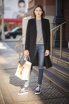 Alexa Chung has a simple spring outfit idea we love - ripped skinny jeans, Vans, a gray sweater, and knee-length black coat. Click for more looks to inspire your style right now.