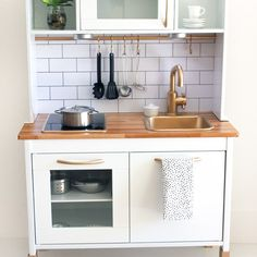 I love spotting a good IKEA hack. And this one blew me away. Sara Eslami took the DUKTIG play kitchen ($99, check out the before) and gave it an update using only: Ikea TAG Handles, Butcher Block Contact Paper, LED stick-on lights, spray paint (white, gold, and primer), poster board and sharpie...