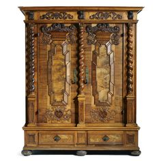 A FINE SOUTH GERMAN WALNUT WARDROBE BAROQUE, LATE 17TH CENTURY the front applied with spirally twisted half-columns flanking the two doors, retaining good wrought iron mounts of blued steel on the interior, a pair of drawers fitted inside the bottom raised on flattened spherical feet, in four sections
