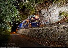 North of Romney Station, a southbound B&O passenger extra passes a steep rock outcrop and vintage stone wall, on its late evening trip through the scenic, and narrow Potomac River Valley. The road paralleling the right of way leads to many summer camps along the river, a common sight in this part of West Virginia.