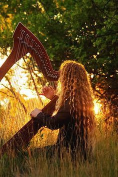 Female harpist with face hidden by very long curly blonde hair plays large Celtic harp in meadow at sunset.  Photo by Anna Goren