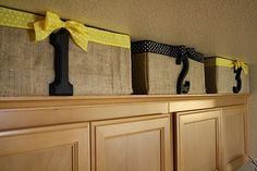 Cardboard boxes and burlap for that nasty empty space above the cabinets. Use to store picnic & party supplies, rarely used big bowls & platters, etc. to free up cabinet space!