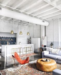 White brick walls and dark tails . Open plan industrial kitchen and living room.