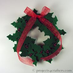 Simple mini Christmas wreath made by cutting out holly leaves from green felt and attaching them to a polystyrene ring with long pins. Use large red beads as berries and finish with a red ribbon bow.