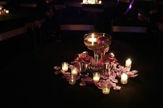 A giant martini glass with a single floating candle and a single bluebird fresh rose. Around the base of the martini glass with had 3 silver mint julep cups with 3 lilac silk roses and silk rose petals on the table and a 12 piece votive candle set – $50 centerpiece