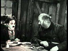 """""""Gold Rush"""" es la pelicula más famosa de Charlie Chaplin, en 1925. En el video solo se muestra una de las escenas más características, cuando Chaplin hace la cena de Acción de Gracias, pero deben comer un zapato. Canibalismo y homicidio es uno de los temas oscuros que conseguimos en éste film de comedia, terminando con un final trágico."""
