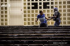 A South Africa anti riot policeman reacts towards a student after masked students enter a building of the Witwatersrand University in Johannesburg on October 10, 2016 to disrupt classes in a bid to shut down the campus. Student protesters at South...