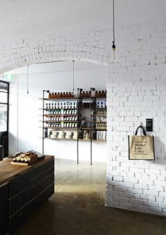 Painted white brick is always gorgeous with industrial hardware. ttott.co #shoptalk