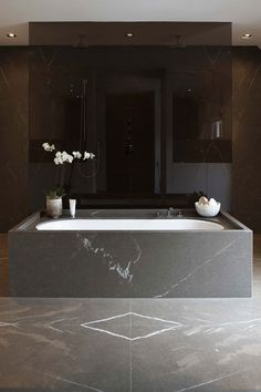 Black glass shower, book-matched stone floor