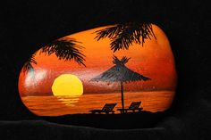 Hand painted rock featuring an orange toned sunset at the beach with two beach chairs, sun parasol and palm trees overhead. All painted in acrylic paints and finished with two coats of polyurethane varnish so can be used inside as a paperweight or decoration, or outdoors. All my