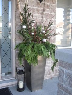 a metal urn with evergreens, pinecones and ornaments