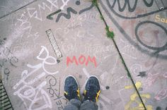 Looking down at 'mom' drawn on a sidewalk by Lucas Saugen