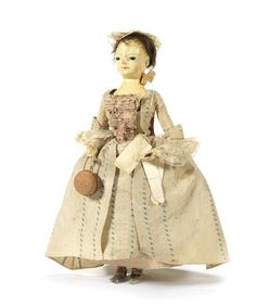 c. 1750 English wooden doll wearing her original cream silk open robe with embroidered dotted green stripes, flounced lace engageantes, two petticoats and lawn chemise, over a boned cream silk corset, pale blue damask slippers with pink rosettes, lace cap, damask stomacher, straw work bag, hanker-chief and kid gloves.