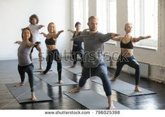 Group of young sporty people practicing yoga lesson with instructor, stretching in Warrior Two exercise, Virabhadrasana 2 pose, working out, indoor full length, students training in club, studio