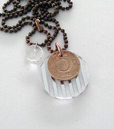 En gammal 5-öring i koppar ihop med spegelplexi har blivit ett nytt halsband. An old Swedish copper coin with plexiglass has become a new necklace.