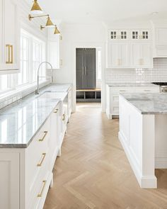 white kitchen with herringbone floors and brass lights