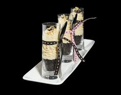 A photo of 4 mini Peanut Butter Parfaits served in shot glasses with pink and brown ribbon tied around glasses holding the dessert spoon.