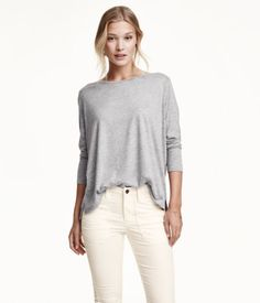 Wide-cut, glittery top in soft jersey with long sleeves and slits at sides. Slightly longer at back.