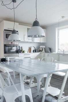 White Scandinavian kitchen with industrial lamps and DIY table, Tolix A chairs and Stokke Tripp Trapps