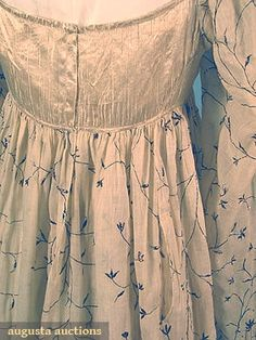 METALLIC EMBROIDERED GOWN, c. 1805  Go Back Lot: 357 March/April 2005 Vintage Clothing & Textile Auction New Hope, PA Cotton mull w/ floral embroidery in metallic thread, bodice in cream silk satin, B 32, Hi W 30, L 51-57, (bodice silk seperating, small brown spots) good.