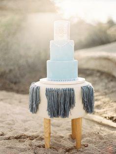 Boho fringed stool + cake: http://www.stylemepretty.com/california-weddings/twentynine-palms/2016/04/19/a-boho-desert-inspiration-shoot-with-major-dress-drama/ | Photography: Lucy Munoz - http://www.lucymunozphotography.com/
