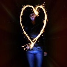 """The Sparkler"", A Long exposure, my first attempt at  experimenting with the technique known as ""light painting"".I placed a torch on the ground illuminating my model ! and she waved a single sparkler in the shape of a heart whilst I took a long exposure and added slight zoom.  Canon EOS 350D. f 1.8  50mm Lens @ f/3.0. Tripod & remote shutter release switch.  Bulb Mode ; single 6.3 Second Exposure. ISO 100. © M.Hughes  Photography 2014"