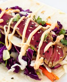 Ahi Tuna Tacos loaded with cabbage, cilantro,radishes and topped with a spicy sriracha mayo.
