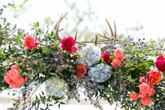 Flowers and Antlers on a Birch Wedding Arbor