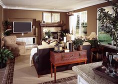Rich mocha walls surround this cozy living room, sitting two-tone sofas and trunk-style decorative table on a beige area rug over tile flooring. Light brick fireplace in corner features a dark stained wood mantle.