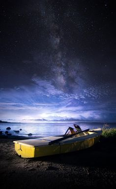 Wow! Boat alone on the lake at night under a dark blue sky. Hope for a new dawn