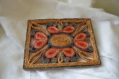 A great straw trivet in rectangular shape, measuring 8.25 x 6.25  Pattern seems to be floral design inside rectangle. Colors are bluish gray
