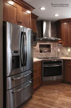 Kitchen remodel by Renovisions. Induction cooktop, stainless steel appliances, cherry cabinets, shaker cabinets, under cabinet lights, tuscan-clay-look porcelain tile backsplash, quartz countertop, hardwood floors, recessed lights, corner stove.