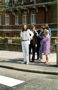 """Picture taken by Linda McCartney as the Beatles were preparing for their """"historic"""" shot on August 8th, 1969.     The Beatles crossed Abbey Road several times for photographer Iain MacMillan and in 4 of the 6 photographs McCartney walked barefoot; for the other two he wore sandals. Paul chose the 5th photo for the album cover.     Link for article and the six photos:  http://www.beatlesbible.com/1969/08/08/the-abbey-road-cover-photography-session/"""