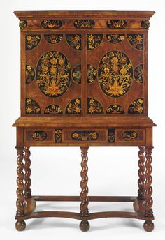 A DUTCH BAROQUE WALNUT AND FLORAL MARQUETRY CABINET ON A LATER STAND  with a rectangular top above a cushion molded frieze drawer and a pair of doors enclosing an arrangement of doors flanking a door enclosing three recessed drawers; the stand fitted with a drawer and raised on turned legs joined by a stretcher, the whole veneered with floral marquetry incorporating spring and summer flowers; incorporating some 17th century elements