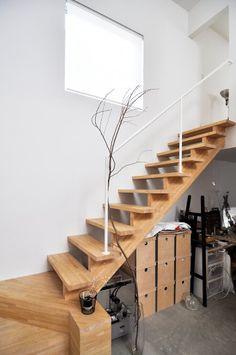 しっかりしたつくりの木の階段が安心感を与える。右下が奥さんの作業テーブル。