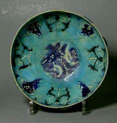 Superbe coupe hémisphérique sur piédouche, en céramique à engobe turquoise.  Décor de bouteroles ajourées sur le bord externe ; motifs peints en noir et bleu lapis (Restaurations) Iran (Khorassan) 13è siècle  Diam.19 cm