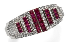 A retro ruby and diamond bangle bracelet, CARTiER - the hinged bangle centering step-like terminals of pavé-set round brilliant-cut diamonds and channel-set rubies; signed Cartier, no. 9253; estimated total diamond weight: 7.00 carats; estimated total ruby weight: 11.50 carats; mounted in platinum; diameter: 2 1/8in.