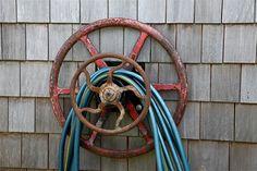 vintage steering wheels used as hose holders