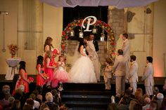 a flower adorned arch with the newlyweds initial for a wedding altar - thereddirtbride.com - see more of this wedding here Initial Decor, Girls Dresses, Flower Girl Dresses, Wedding Altars, Newlyweds, Initials, Arch, Wedding Dresses, Flowers