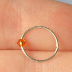Perfect for a November birthday!  This is for a SINGLE hoop ring perfect for your upper ear, nose, eyebrow, or wherever else you have pierced! This is not a cuff, it is an actual piercing ring! The bead on it is a Topaz Swarovski Elements Bicone. It is loose, not glued, on the ring.  $6.25