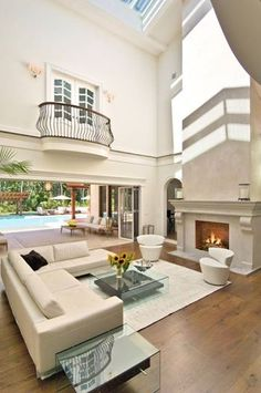 A luxurious, modern living room with cathedral ceilings featuring skylights and a large white fireplace.   Source: http://www.zillow.com/digs/Home-Stratosphere-boards/Luxury-Living-Rooms/