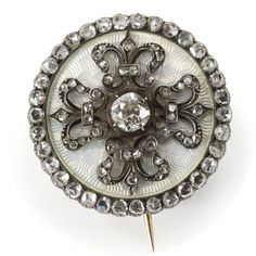 A gold, enamel, and diamond brooch, circa 1900. The circular brooch enameled in translucent oyster over a wavy engine-turned ground, centered with a brilliant cut diamond surrounded with four fleur-de-lys set with rose-cut diamonds, the border also set with rose-cut diamonds. Converted from a button, the added pin and clasp marked with Cyrillic initials MP for Fabergé workmaster Michael Perchin.