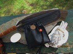 Sacred ceremonial smudge kit with naturally dropped crow feathers, white sage smudge,natural white worry stone, carved buffalo bone. 10 mm wood beads & Oyster smudge shell from Little River, SC. Hand wrapped with quality Brown leather. Smudge feather is 12  Worry pouch is 3 1/4  x 2 1/2  the worry stone fits nicely inside this drawstring pouch ! Pouch was made with quality black deerskin leather Brown wood beads. Brown/ dk. Brown leather straps. *****  PLEASE NOTE: I can add a leather cord…