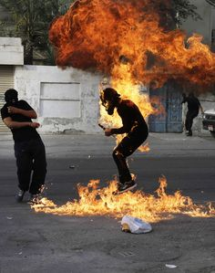 """A Bahraini anti-government protester is engulfed in flames when a shot fired by riot police hit the petrol bomb in his hand that he was preparing to throw during clashes in Sanabis, Bahrain, Thursday, March 14, 2013. Protests and clashes erupted in opposition areas nationwide Thursday with government opponents observing a """"Dignity Strike"""" _ blocking roads, closing shops, protesting and staying home from work and school _ called by the more radical February 14 youth group. (Hasan J"""