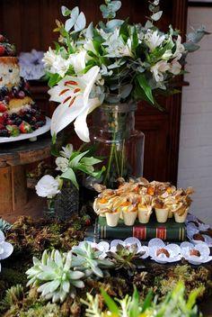 Mesa de bolo rústica com suculentas, muito verde e arranjo de flores brancas com lírios e folhas de eucalipto. Naked cake em carretel rústico e docinhos em livros vintage decoraram esse mini wedding em restaurante de São Paulo.