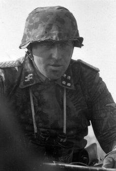 SS-Sturmbannführer Gustav Knittel, commander of SS-Panzer-Aufklärungs-Abteilung 1 of the Leibstandarte Division, photographed confering with his men during Operation Zitadelle in July 1943.