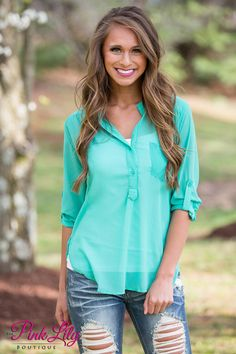 We love this lightweight blouse - it is so perfect for relaxing on the porch all summer long! The cool shade of mint is so trendy and easy to style with jeans or jeggings! It also features two buttons, a pocket, and rolled sleeves!